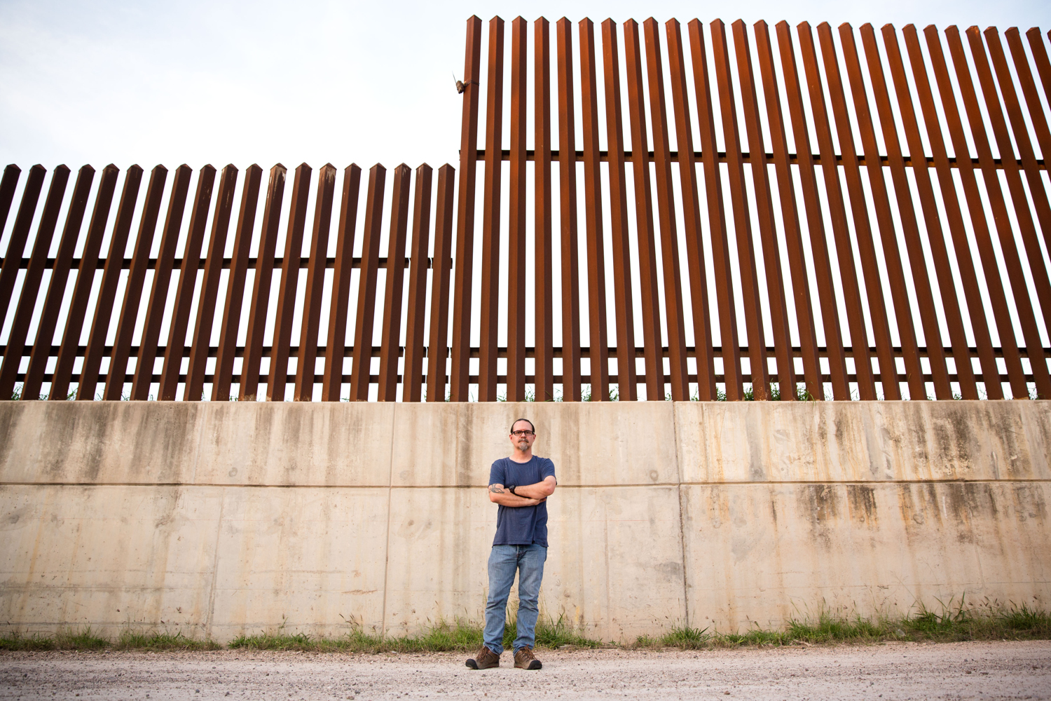 Scott Nicol, co-chair of the Sierra Club's Borderlands Campaign, stands in front of a concrete levee topped by the border fence atop in Hidalgo County. Environmentalists, along with the U.S. Fish and Wildlife Service, say the barrier endangers wildlife because animals can't reach dry land during floods.