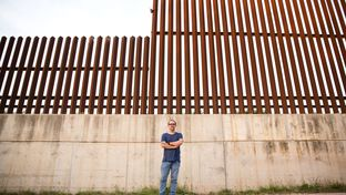 Scott Nicol, co-chair of the Sierra Club's Borderlands Campaign, stands in front of the border fence in Hidalgo in far South Texas. This section, which sits atop a levee, runs between a national wildlife refuge and a local nature center.