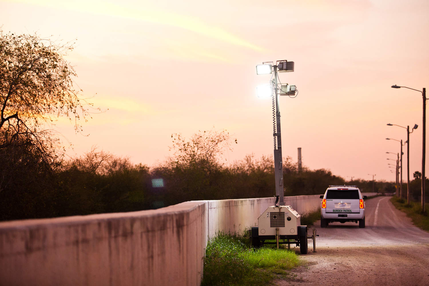 At sunset, a Customs and Border Patrol agent places noisy, generator-powered floodlights along a levee that ties into a segment of border fence in Hidalgo, Texas.