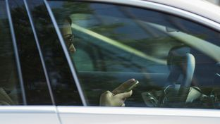 A woman checks her phone while driving in Austin. A statewide texting-while-driving ban goes into effect Sept. 1, 2017.