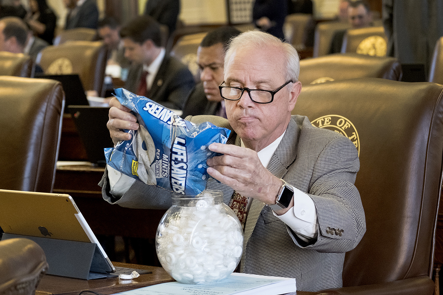 Rep. Gary Elkins, R-Houston, fills a candy bowl.
