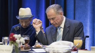 Gov. Greg Abbott prays with event organizer Evelyn Davison at the 66th annual Texas State Prayer Breakfast in Austin on May 1, 2017. Davison has organized the event for the last 43 years.