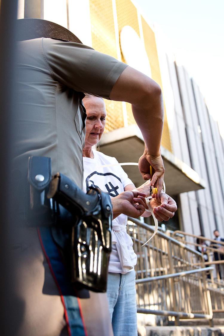 A Department of Public safety officer removes a zip tie from a protester's wrists in Austin on May 1, 2017.
