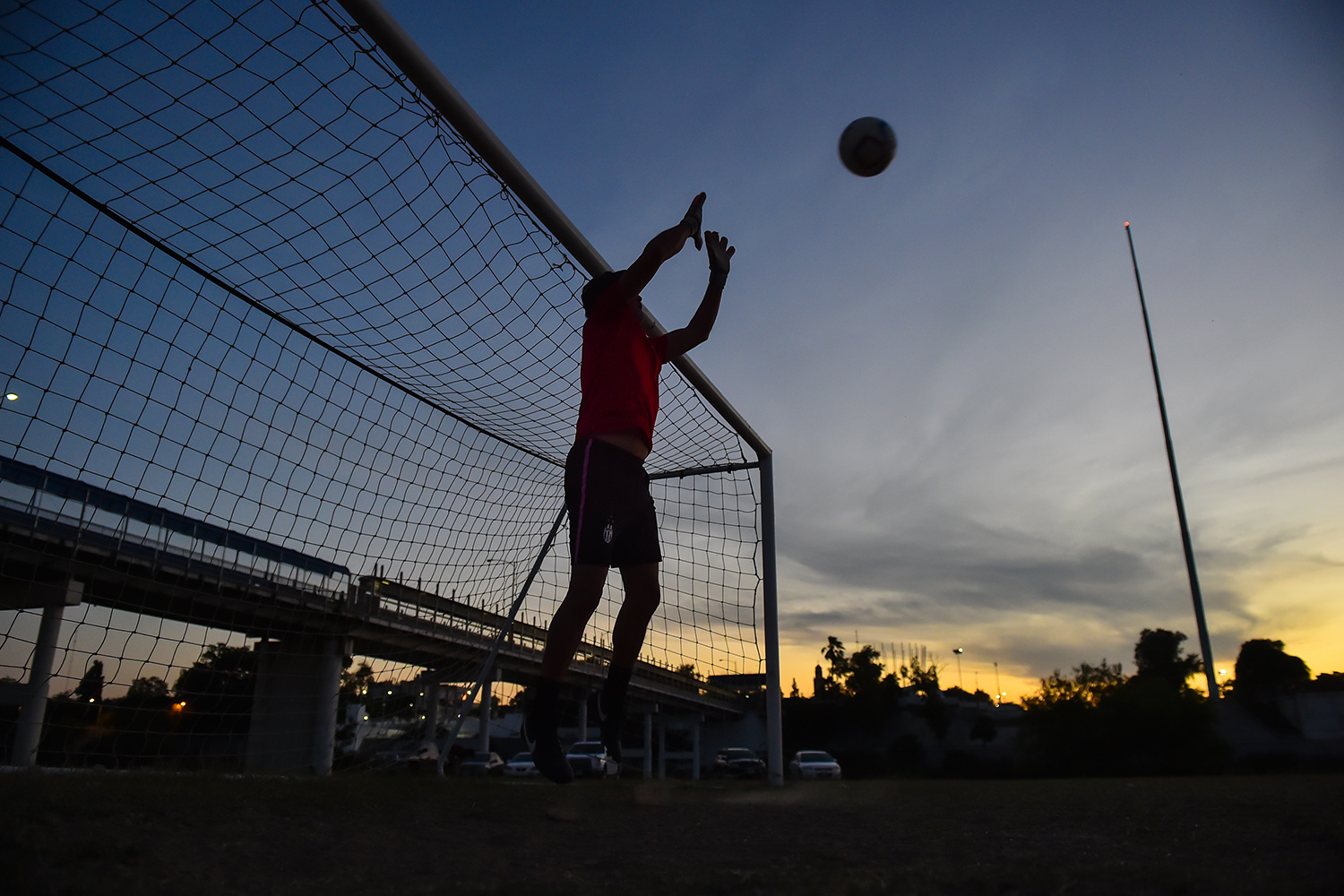 Members of the Twin Cities FC practice at twilight on an Eagle Pass soccer field between the Rio Grande and the current border fence. Piedras Negras, Mexico, is in the background.