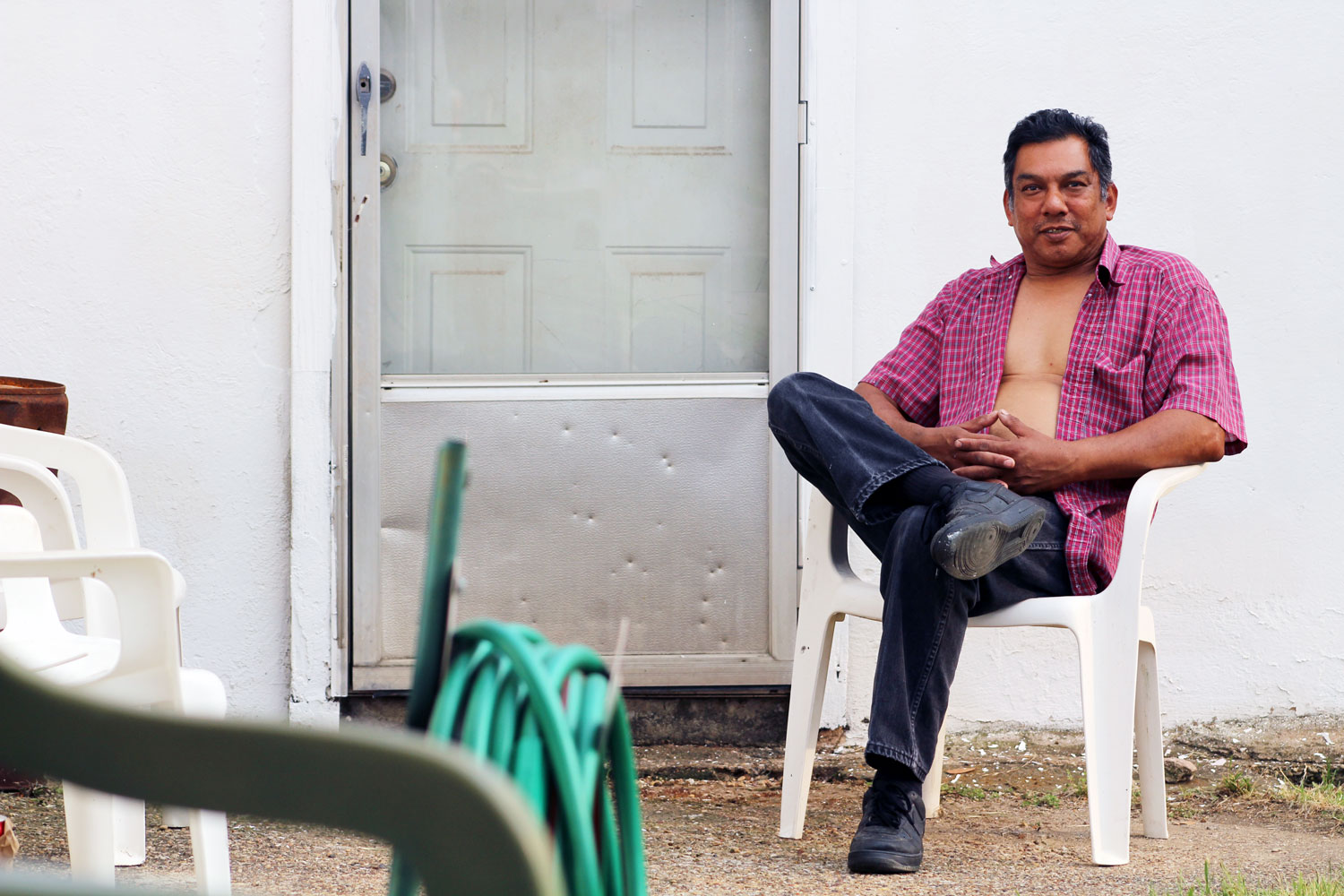 Pete Hernandez relaxes on a neighbor's porch in May 2017. Hernandez has lived in West Dallas his entire life. His property value recently skyrocketed, leaving him with a tax bill that almost tripled in one year.