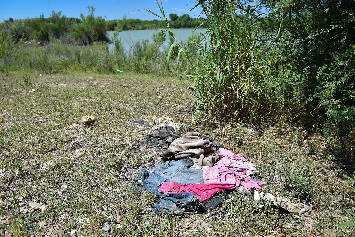 A pile of clothes near the river on Salvador Salinas's 500-acre ranch in Maverick County. Migrants often discard used clothing after making it to the north bank of the Rio Grande.