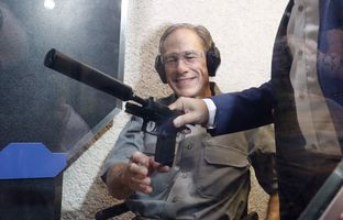Gov. Abbott prepares to fire a silencer-equipped Sig Sauer P320at a shooting range in Austin after signing Senate Bill 16, which reduces the first-time fee for a license to carry handguns, on May 26, 2017.