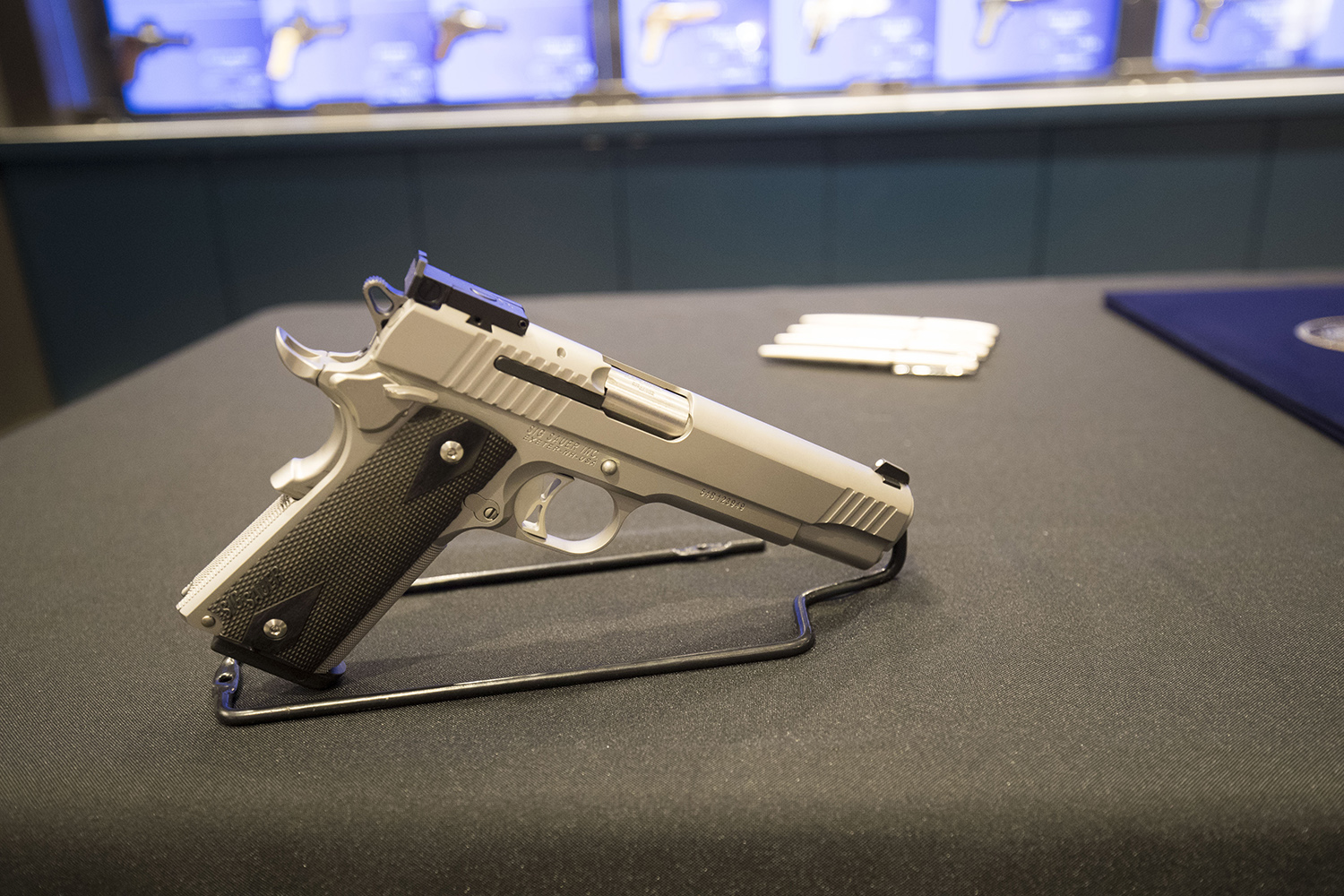 A Sig Sauer P320 9mm handgun, with Gov. Abbott's signing pens behind it, at a shooting range in Austin. The governor signed Senate Bill 6, which reduces the first-time fee for a license to carry handguns, at the range, on May 26, 2017.