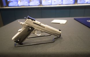 A Sig Sauer P320 9mm handgun, with Gov. Abbott's signing pens behind it, at a shooting range in Austin. The governor signedSenate Bill 6, whichreduces the first-time fee for a license to carry handguns, at the range, onMay 26, 2017.