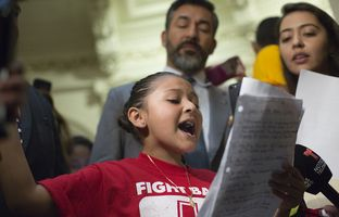 "State Reps. Tomas Uresti, D-San Antonio, and Ramon Romero, D-Fort Worth, stand beside 9-year-old Wendy as she gives a speech protesting Senate Bill 4, the ""sanctuary cities"" bill, on May 29, 2017."