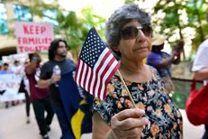 A woman demonstrating against Senate Bill 4, the so-called sanctuarycities law, waves a flag during a march near the San Antonio Riverwalk on June 26, 2017. U.S. District Judge Orlando Garcia is hearing arguments fromTexas cities and counties challenging the bill, signed into law by Gov. Greg Abbott.