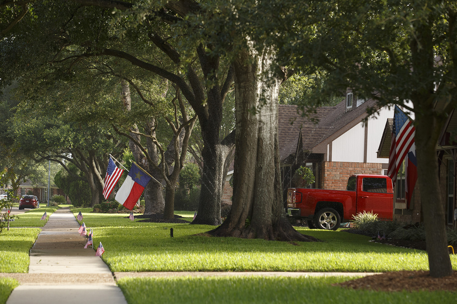 Residents put up flags for the Fourth of July in a neighborhood on the south side of Pasadena on July 1, 2017.
