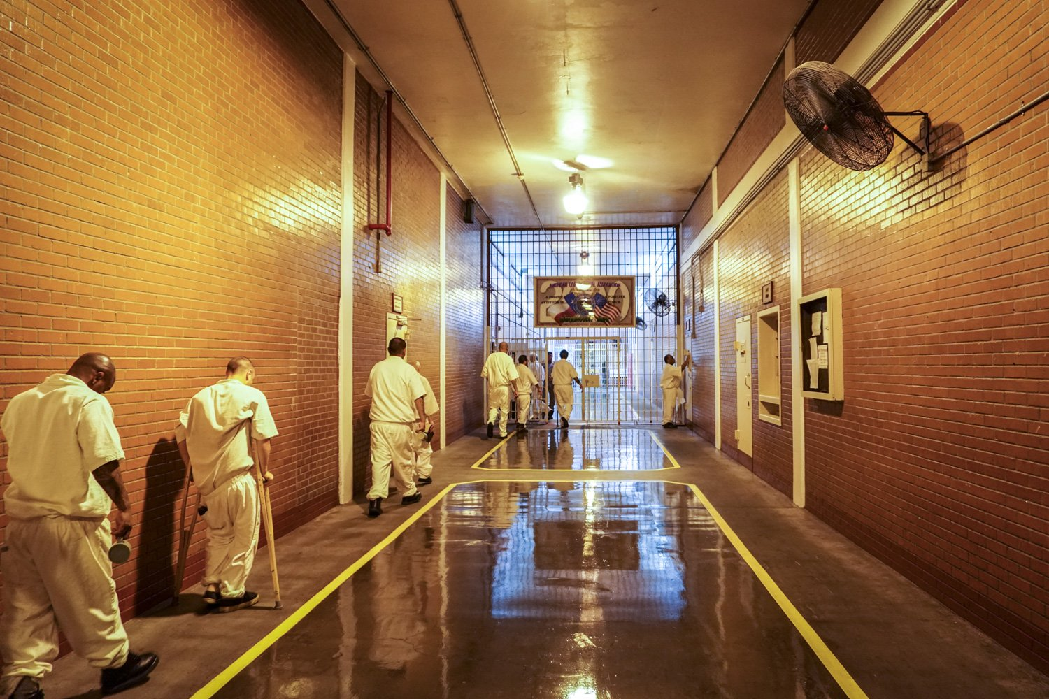 Inmates shuffle past new fans in the Darrington prison's main hallway on a hot July day.