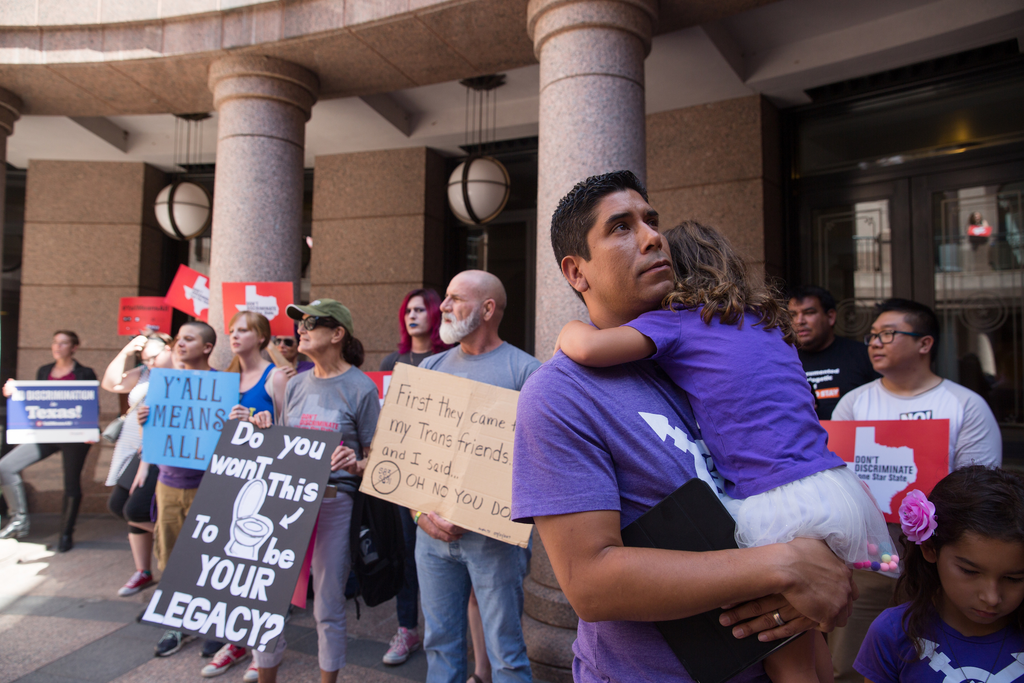 Frank Gonzales holds his daughter after speaking at a rally to denounce bathroom restrictions for transgender Texans on July 21, 2017.