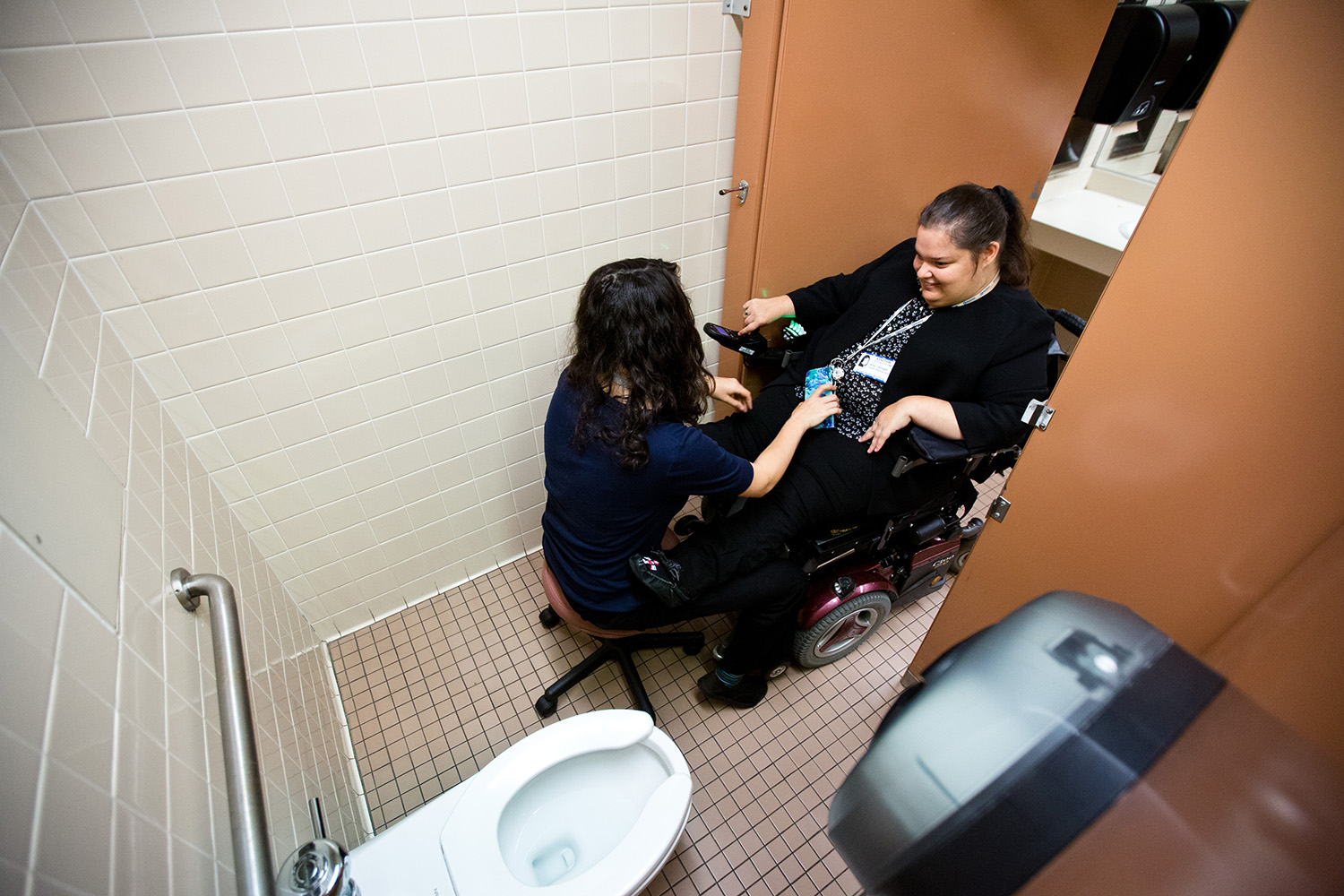 Before a committee meeting in the Texas Health and Human Services building, Amy Litzinger and her attendant, Jamie Massaro, demonstrate that they must leave the accessible bathroom stall door open because it is too small.