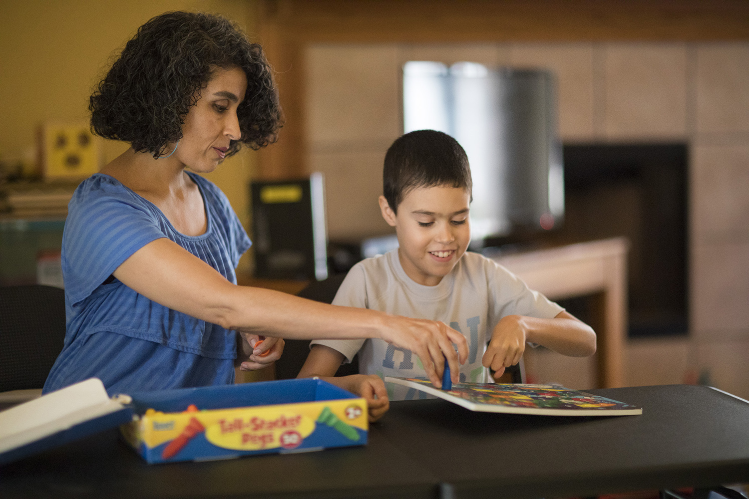 Rosanna Armendariz plays a motor skills game with her son, Octavio, at their home in El Paso, Texas.