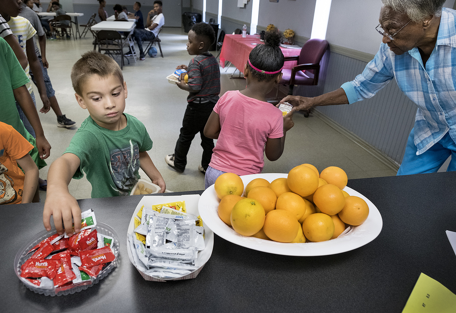 Clara Crawford puts a milk carton on 6 -year-old Jaylynn Uniqe's plate as Ethan Smallwood reaches for ketchup at the Fairview Community Center in Reklaw.