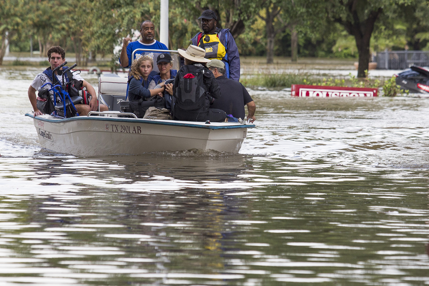 Evacuees flee flooding in a boat with a nearly submerged Houston sign behind them, on Aug, 29, 2017.