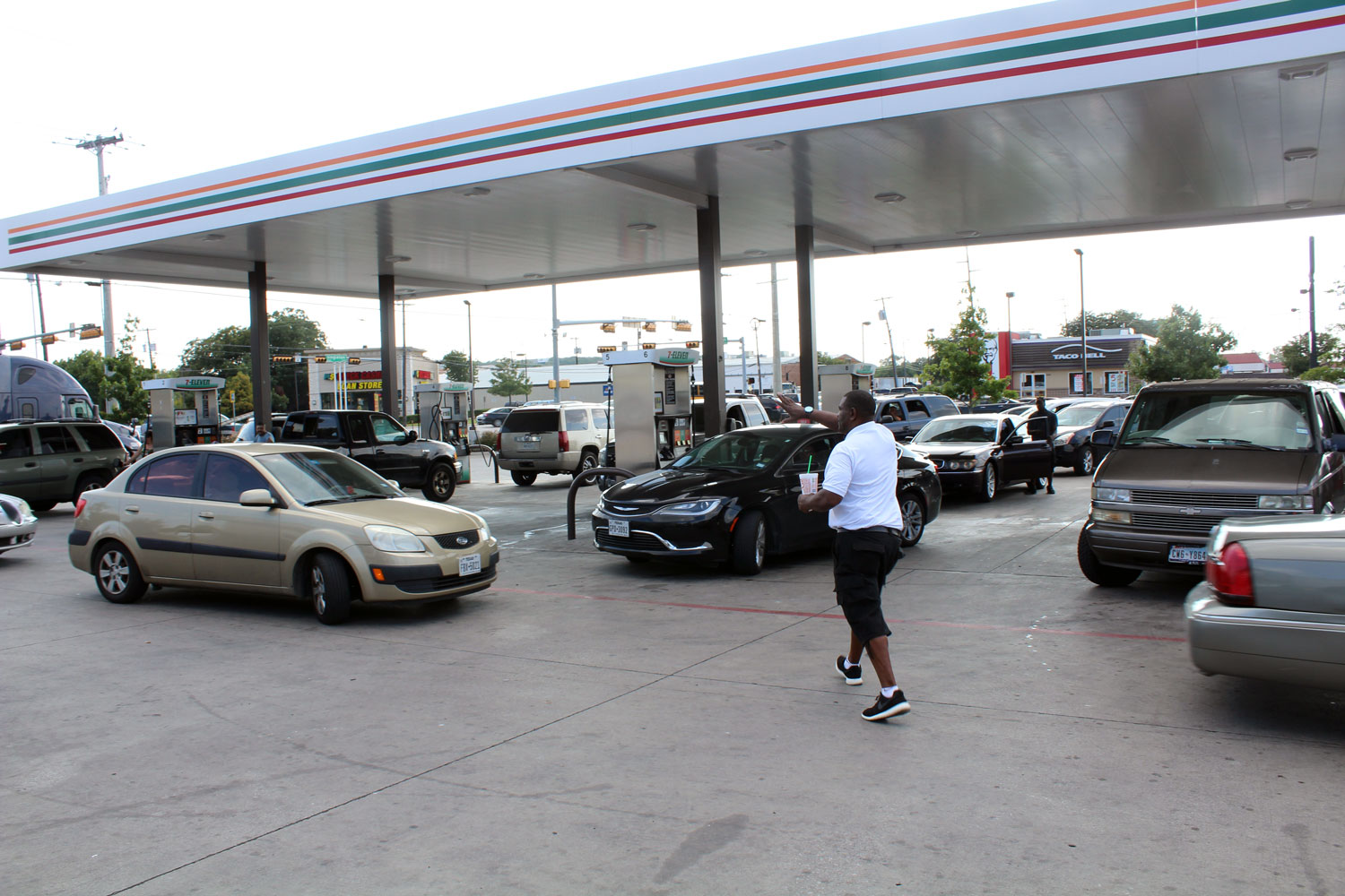 A 7-Eleven employee tries to keep order as cars in West Dallas stream toward gas pumps, trying to fill up amid a panic in Dallas-Fort Worth about rising prices and shortage of fuel in the wake of Hurricane Harvey's impact on oil production on Aug. 31,.