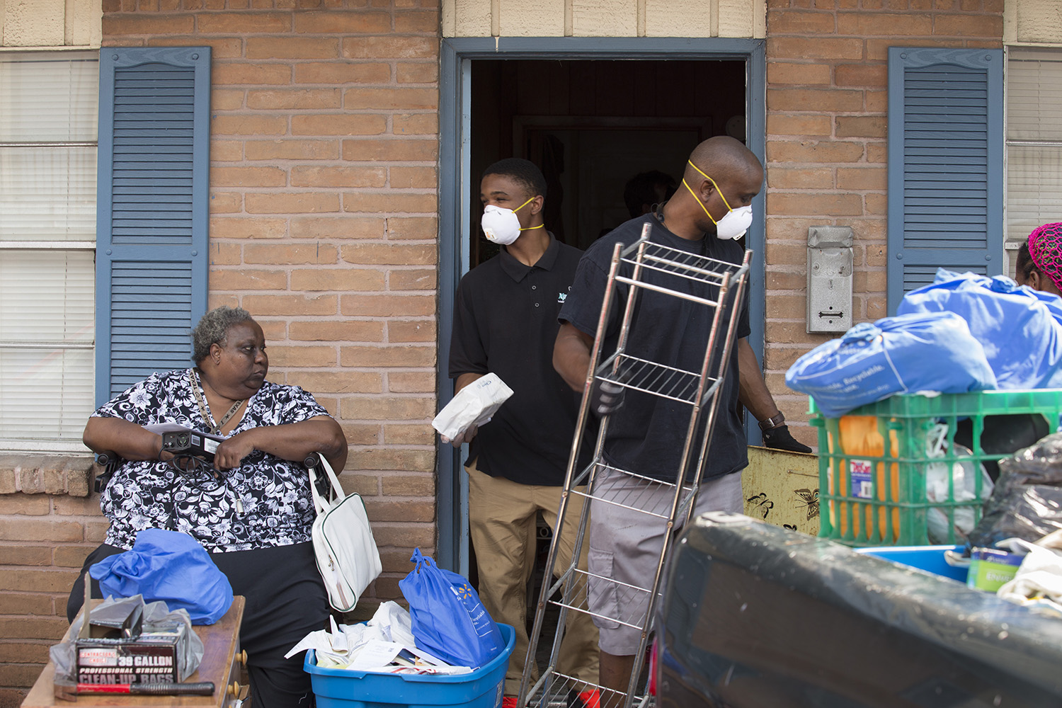Marilyn Wilson, 61, watches as volunteers Jamal Stenson and his son Aahmad clean her flooded apartment out in the Kashmere Gardens neighborhood of Houston on Thursday, Aug. 31, 2017.