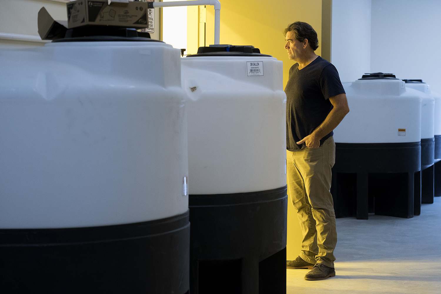 Surrounded by fertigation tanks, Compassionate Cultivation CEO Morris Denton looks into a vegetation room where marijuana plants will begin their growth process.