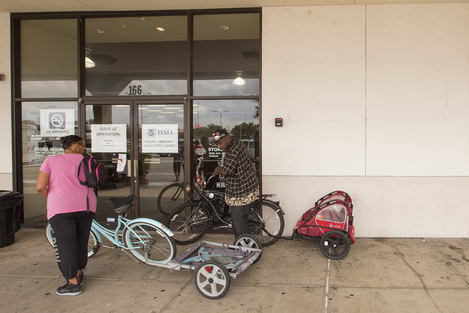 Crystal and Ollie Green rode their bikes to the Beaumont disaster recovery center, where they are seeking help after their apartment flooded.