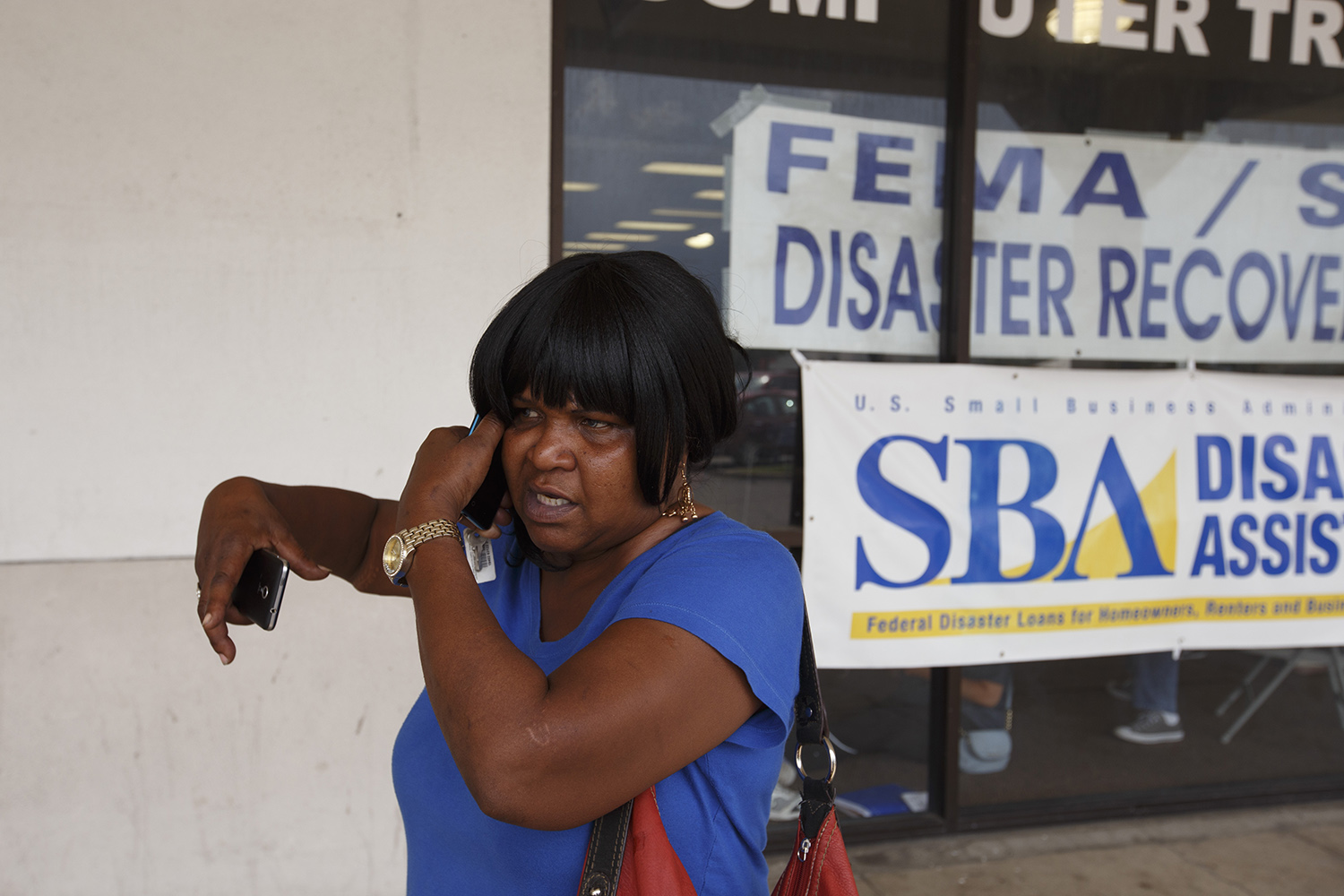 "Veda Armstead takes a phone call outside of a Beaumont disaster recovery center. Armstead said she was able to save some clothing from her flooded house — a few items that were hanging or on higher shelves — but that everything else was ""wiped out."" She's currently moving between the homes of friends and relatives while she figures out whether she'll be able to make repairs on her home."