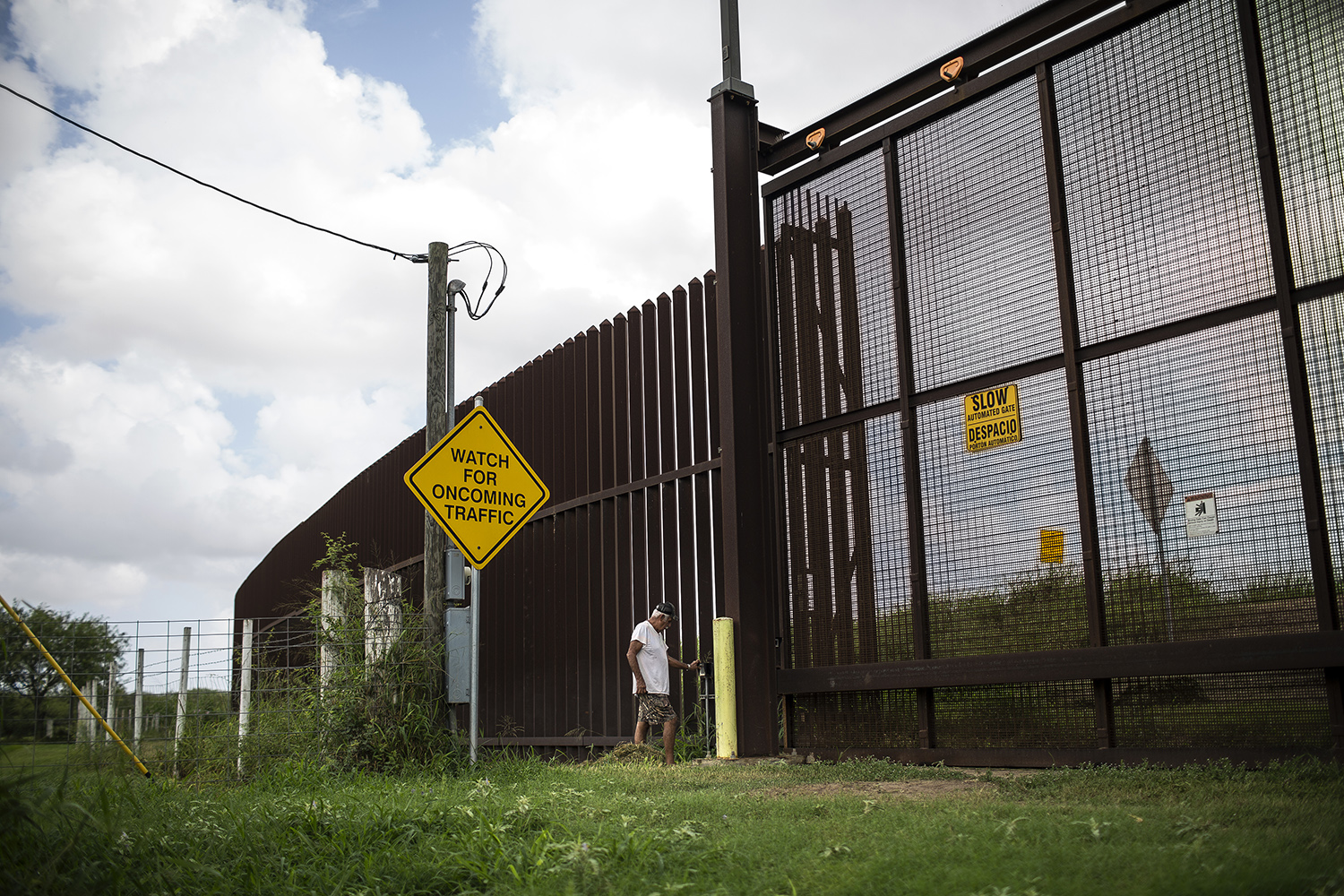 Juan Cavazos enters the code for the gate at the borderwall cutting through his property on Oklahoma Ave. in Brownsville, TX on Aug. 10, 2017.