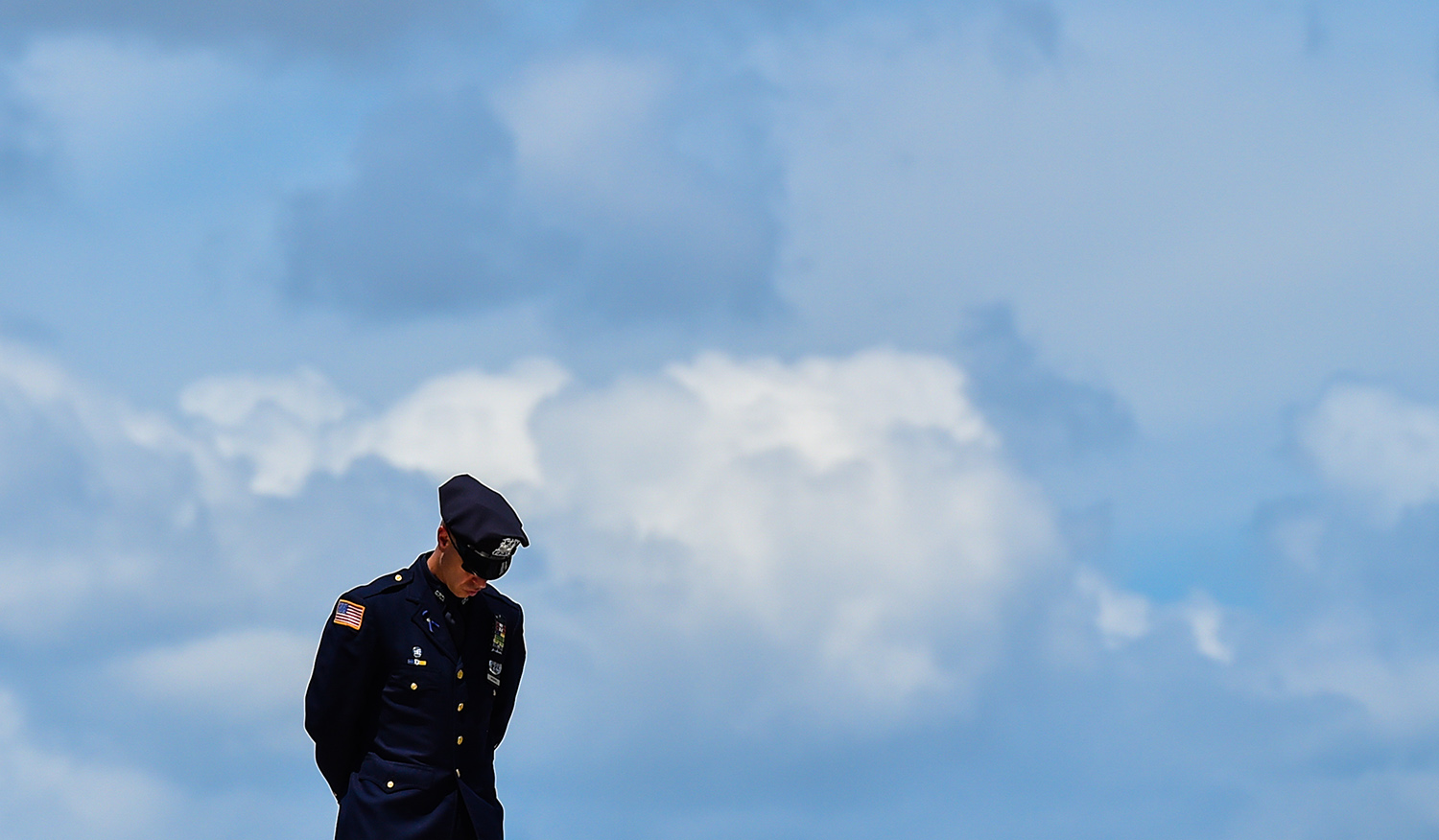 A police officer bows his head during funeral services for slain San Antonio Police Officer Miguel Moreno, in San Antonio on July 7, 2017.