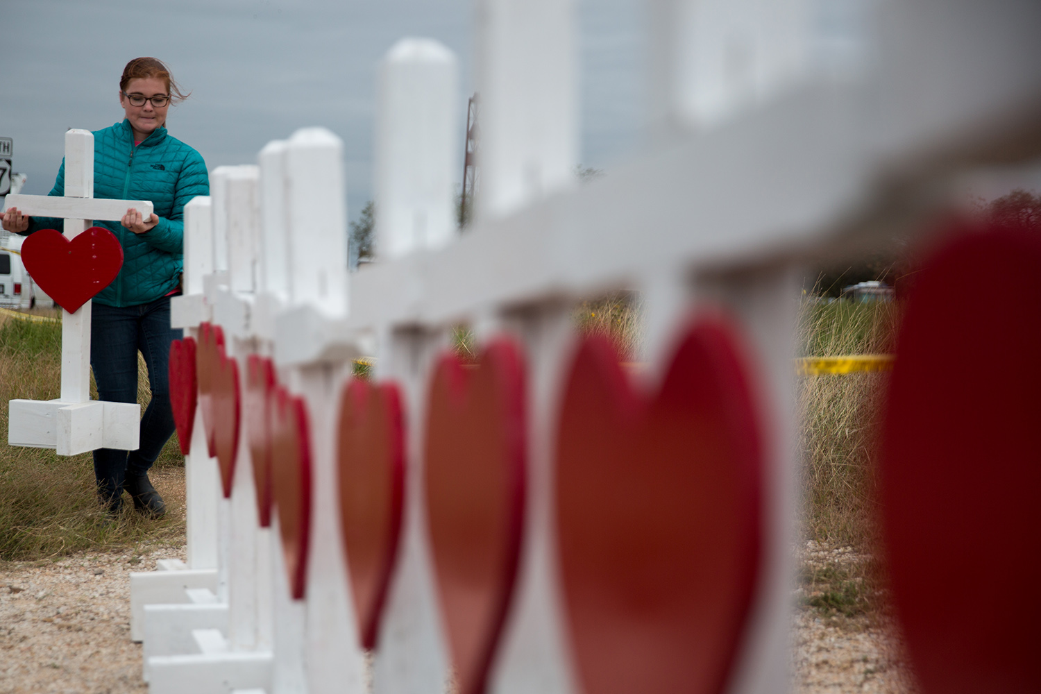 Hannah Krueger adds a cross to a memorial near the First Baptist Church in Sutherland Springs on Nov. 8, 2017, three days after 23 churchgoers were killed in a mass shooting there.