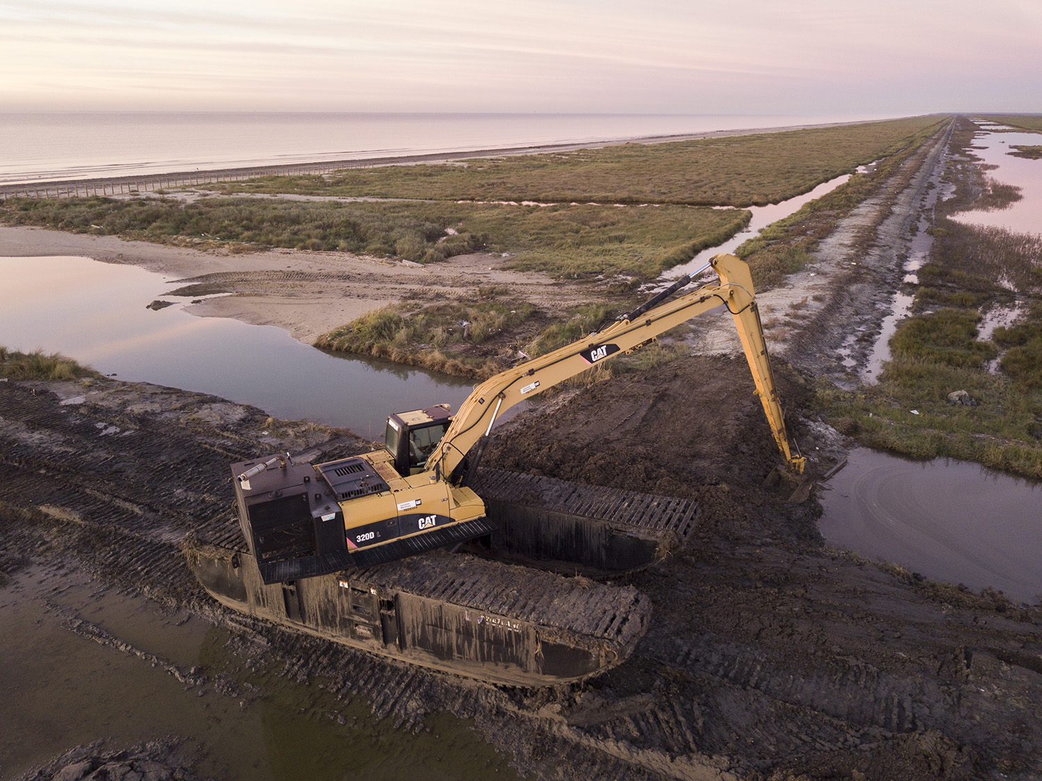 A digger can be seen near a clay berm being built behind the the dunes and beach at the McFaddin Wildlife Refuge near Port Arthur on Wednesday, Dec. 13, 2017.