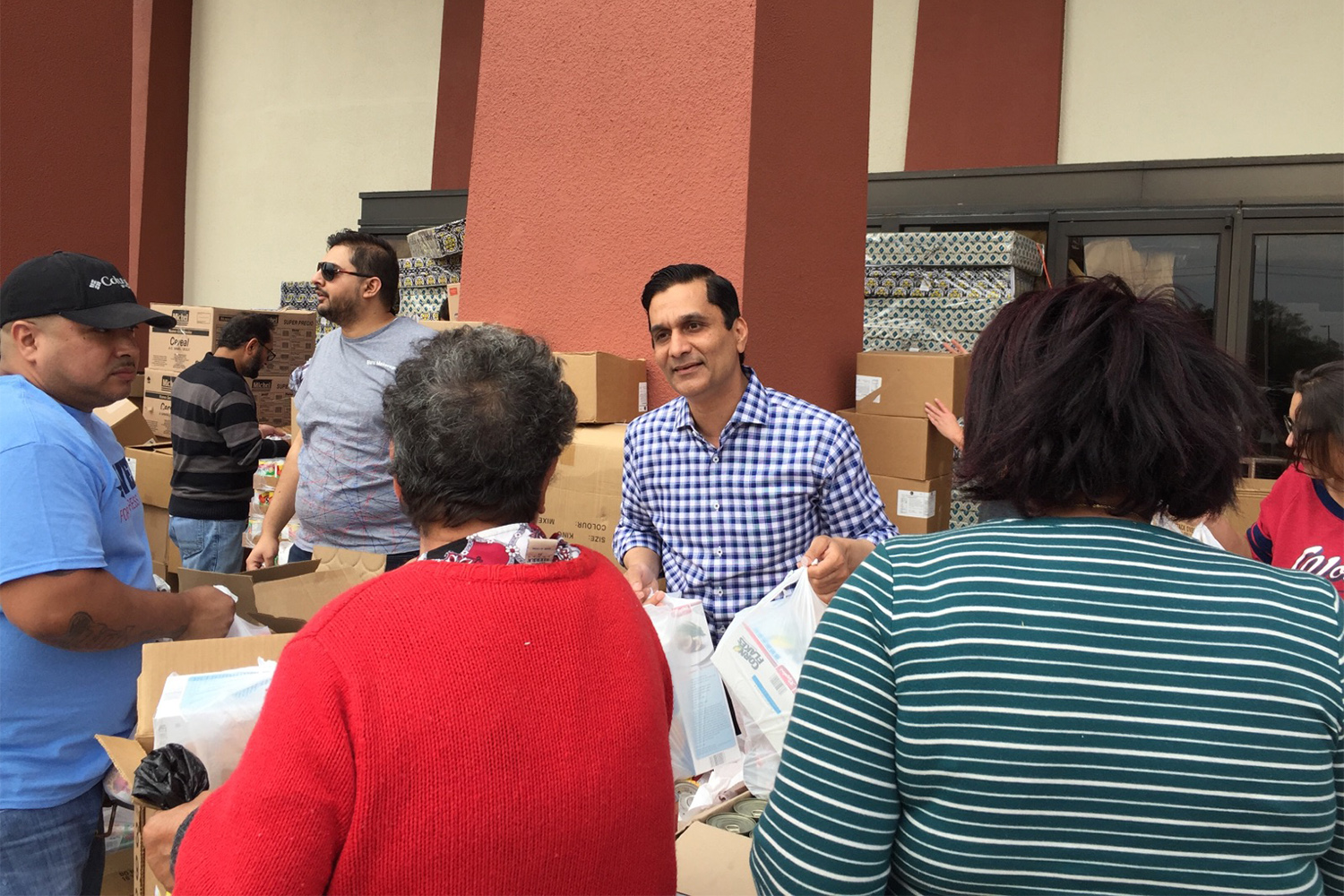 Health care executive and congressional candidate Tahir Javed hands out food in Pasadena on Saturday, March 3, 2018.