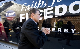 Rick Perry clasps his hands while leaving the Glenn Miller Museum in Clarinda, Iowa on December 27, 2011