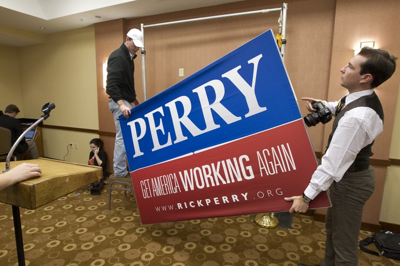 Perry campaign workers take down the final sign of Perry's presidential campaign at the Hyatt Place Hotel where he announced the suspension of his campaign on January 19, 2012.