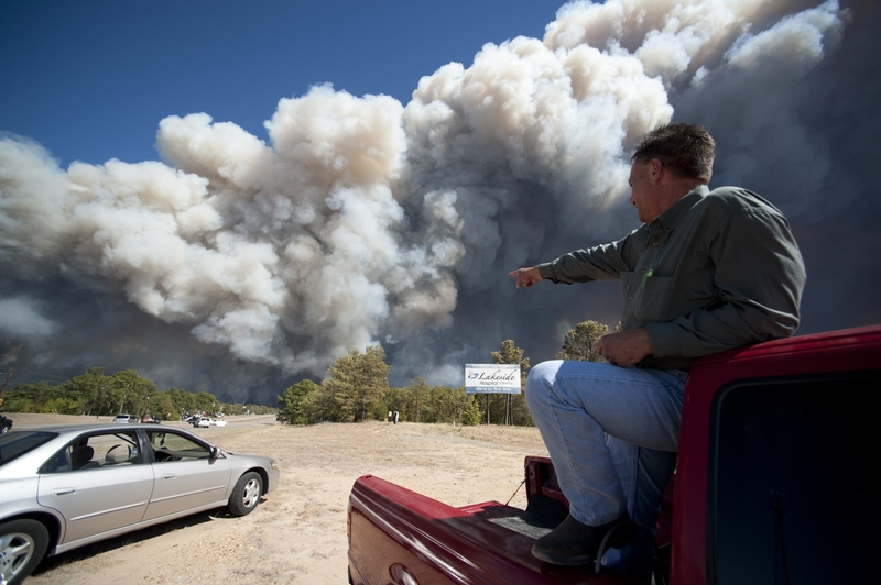 A Bastrop resident points to flames as smoke billows over Texas 71 in Bastrop Country during the wildfires on September 5, 2011.