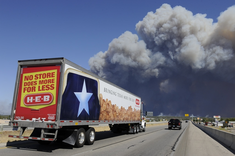 """A grocery truck with the Texas """"Lone Star"""" drives east on Texas 71 toward the wildfire east of Bastrop that is burning out of control on September 5, 2011."""