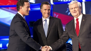 Rick Santorum, left, shakes hands with Newt Gingrich, right, and Mitt Romney watches as the three candidates meet onstage for the CNN Charleston debates on January 19, 2012.