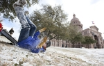 Walker Kohler of Austin wipes out while sledding on the Texas Capitol grounds with his brothers and dad Rob Kohler, a lobbyist, on February 4, 2011