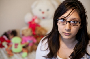 Crystal Martinez sits with items recovered from Child Protective Services at her home in North Austin, Dec. 21, 2010.