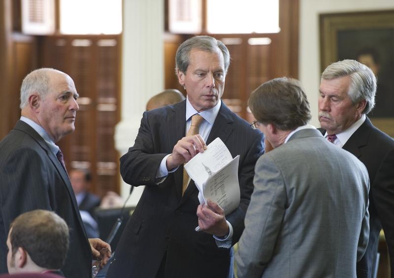 Lt. Governor David Dewhurst (c) goes over legislation with colleagues on the Senate floor April 18, 2011
