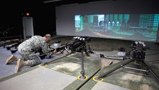 Colonel Crow demonstrating practice techniques at the indoor firing range simulator at Camp Swift, Texas.