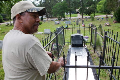 Reverend Rodney Norsworthy, a minister at Mount Olive Missionary Baptist Church, shows the grave of James Byrd, at a cemetery in Jasper, TX on June 15 2012.