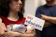 An observer holds a protest sign during testimony at the State Board of Education (SBOE) textbook hearings on Wednesday, May 19, 2010.
