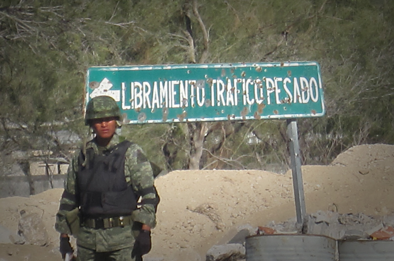 A solider guarding a checkpoint in Ciudad Mier stands in front of a sign riddled with bullet holes.