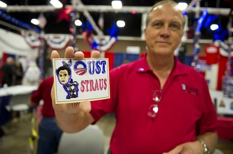 """Mike Zapp of Burleson, TX holds an """"Oust Straus"""" sticker at the Tea Party booth at the state Repulblican Convention on June 7, 2012."""