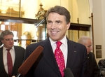 Gov. Rick Perry stops for an impromptu press conference in the hallway behind the Senate chamber on July 19, 2011.
