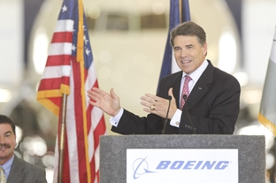 Texas Governor Rick Perry talks about the Texas economy while speaking in front of a Boeing 787 airplane during the ceremonial bill signing of HB3727 in San Antonio on June 23, 2011.