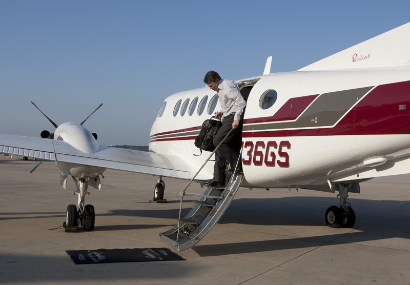 Texas Governor Rick Perry carries his bags off a private plane at  the San Antonio International Airport on November 1, 2010.