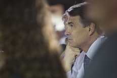Gov. Rick Perry listens to U.S. Rep. Michele Bachmann's speech at an event in Waterloo, Iowa, on Aug. 14, 2011.