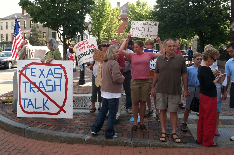 Protesters in Portsmouth await Perry's arrival at Popovers restaurant Thursday, where the Texas governor